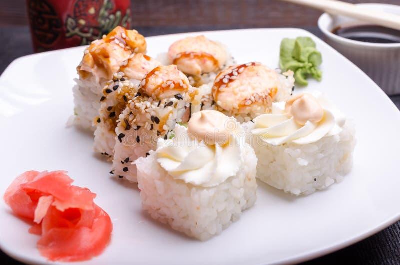 Klipp sushirullar på ett uppläggningsfat med ingefäran och wasabi arkivbilder