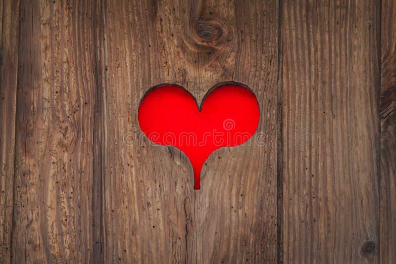Klipp ut gammal träröd hjärtaform arkivfoto