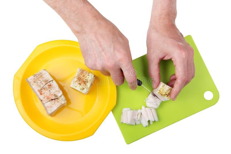 Klippa det djupfrysta salta grisköttet späcka in i tunna skivor för en sandwi royaltyfri bild