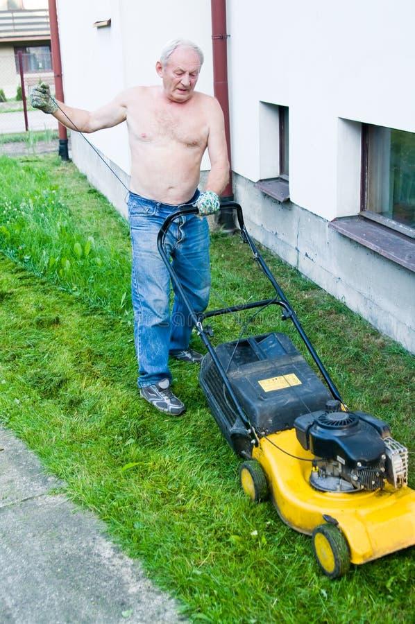 klippa gräsmangräsklippningsmaskinen fotografering för bildbyråer
