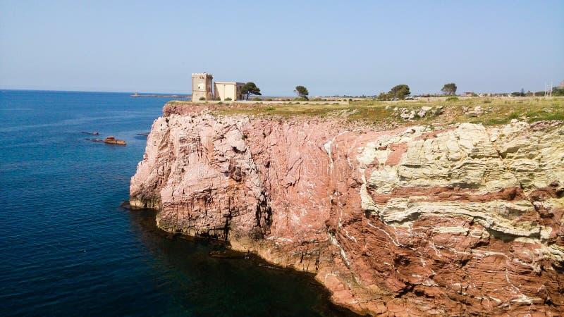 Klippa med det gamla tornet och det blåa havet royaltyfri bild