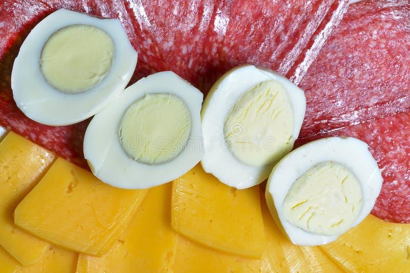 Klippa ost och korven, klippte kokta ägg i halva Begrepp av gastronomisk bakgrund, ingredienser för en smörgås, bakgrund för arkivfoton
