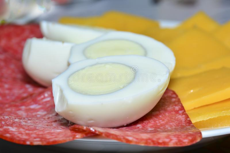 Klippa ost och korven, klippte kokta ägg i halva Begrepp av gastronomisk bakgrund, ingredienser för en smörgås, bakgrund för arkivbild