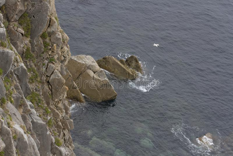 Klippa som badas av havet arkivbild