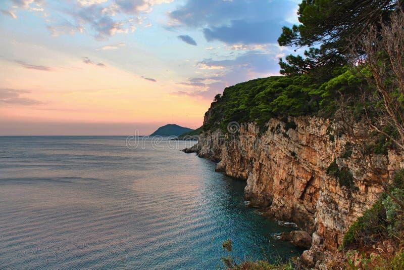 Klippaframsida med havet och en härlig solnedgång med fåglar som flyger i himlen arkivfoto