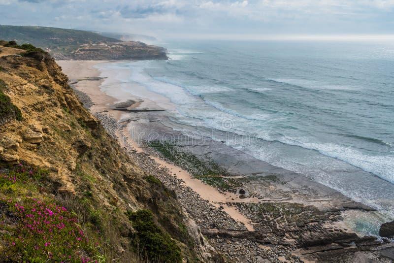 Klippan med blommor bredvid Fozen gör den Lizandro stranden, flyg- sikt av seascape med berg på horisonten, Ericeira - Mafra PORT royaltyfri fotografi