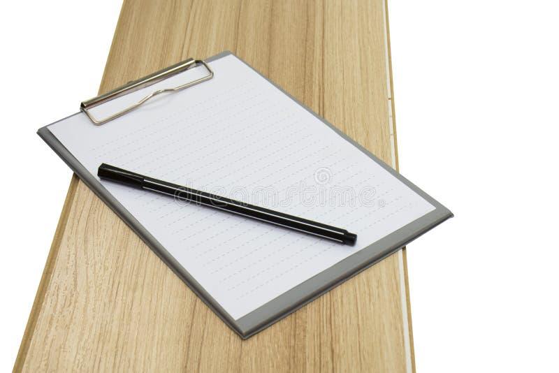 Klippbrett und -stift auf Holz stockbilder