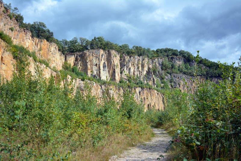 Klippe am alten geschlossenen Abstieg und an überwuchertem Sandstein und Rhyolithsteinbruchgrube im Odenwald-Gebirgszug in Deutsc stockfotografie