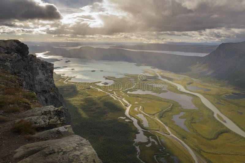Klippe, die großes Flussdelta in der Seeherbstlandschaft mit Regen von den Wolken übersieht stockbilder