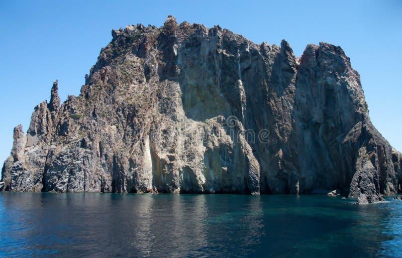 Klippe mitten in dem Meer stockfotos