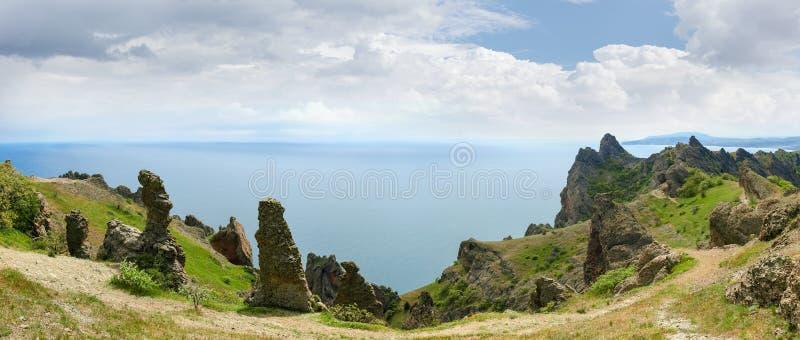 Klippen des vulkanischen Ursprung über dem Seepanoramablick stockbild