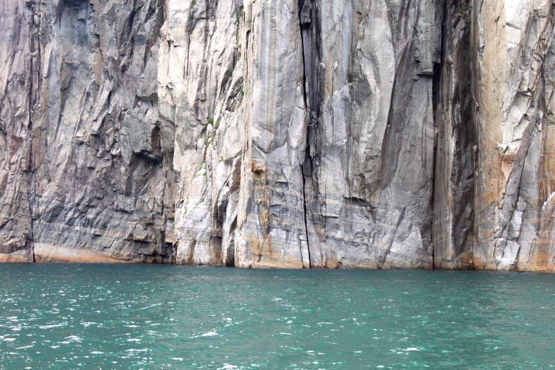 Klippen gegen das helle Fjord-Wasser lizenzfreies stockbild
