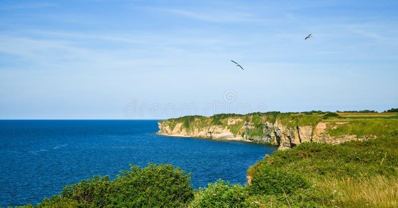 Klippen Pointe du Hoc im klaren Himmel und im ruhigen See Frankreich lizenzfreie stockbilder
