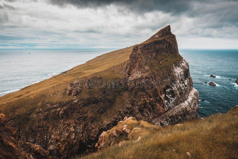 Klippen und das Dorf auf der Insel von Mykines, F?r?er stockfotografie