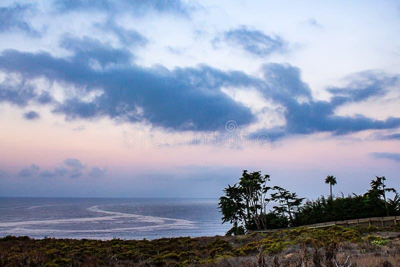 Klippenansicht von Pazifischem Ozean mit Sonnenaufgang, Palmen und Zypresse lizenzfreies stockfoto