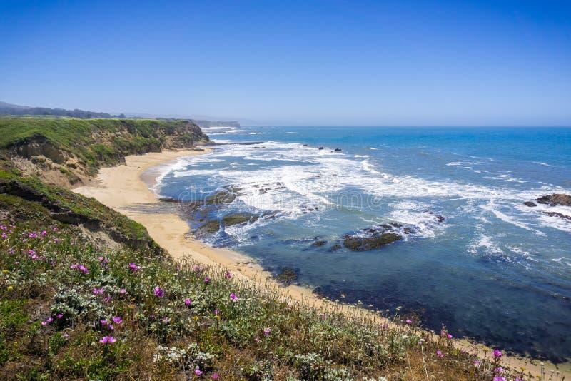 Klippor och sandig strand på Stilla havetkustlinjen fotografering för bildbyråer