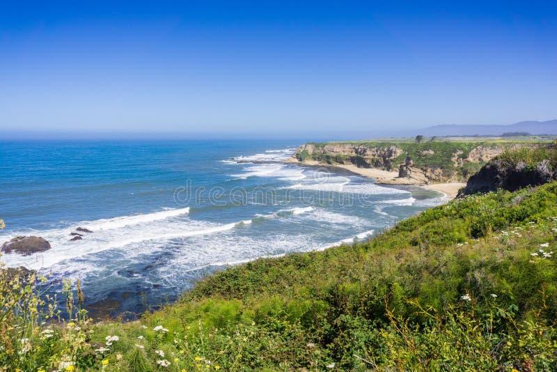 Klippor och sandig strand på Stilla havetkustlinjen arkivbilder