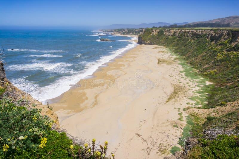 Klippor och sandig strand på Stilla havetkustlinjen arkivfoto