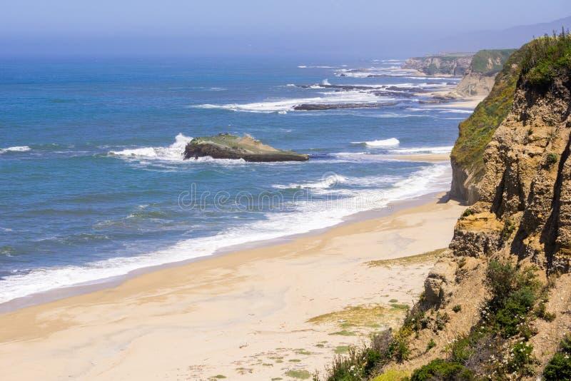 Klippor och sandig strand på Stilla havetkustlinjen royaltyfri fotografi