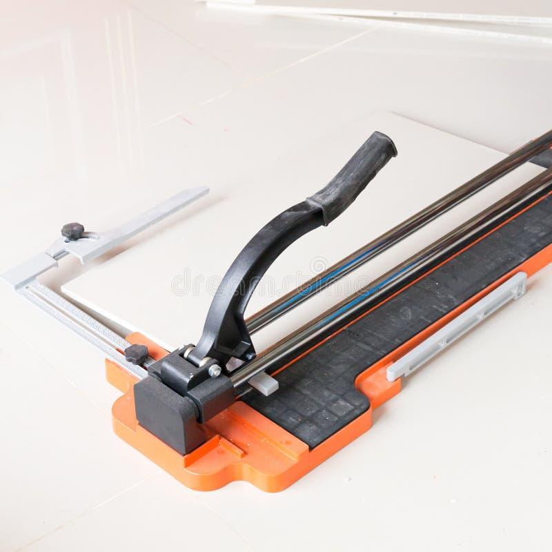 klippprocess för keramisk tegelplatta genom att använda en manuell skärare arkivfoton