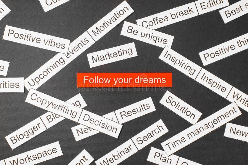 Klippt pappersinskrift att följa dina drömmar på en röd bakgrund som omges av andra inskrifter på en mörk bakgrund Ord CLOUD arkivfoto