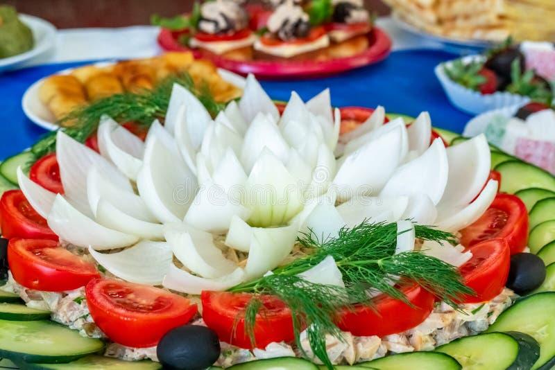 Klippta grönsaker för en sallad close upp Spansk peppar, lök, lövrika gräsplaner, oliv, tomat och gurkor cutted i stycken arkivfoto
