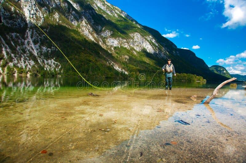 Klipskt fiske för fiskare på laken Bohinj royaltyfria foton