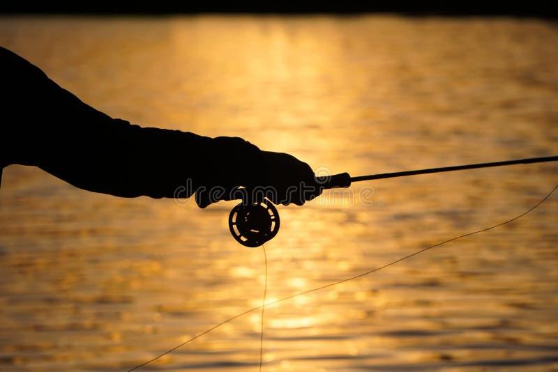 Klipskt fiske för sommarsolnedgång arkivfoton