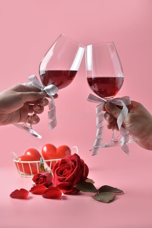 Klirra exponeringsglas av rött vin i händer, med den röda rosen på botten på rosa bakgrund Begrepp av dagen för valentin` s arkivfoto