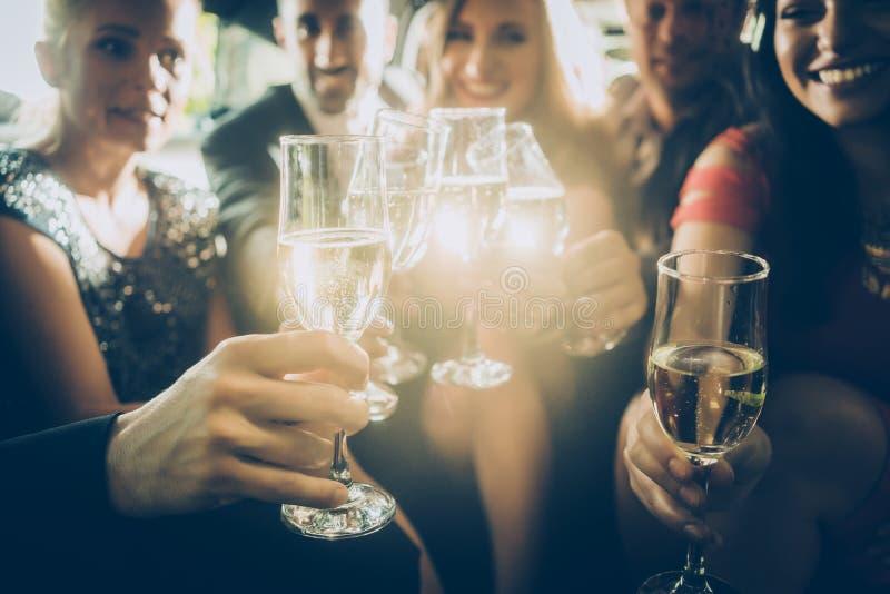 Klirrende Gläser der Parteimenge mit Champagner lizenzfreie stockfotos