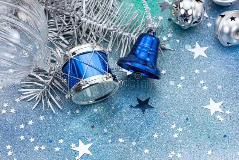 Klirrklockor och silvervalsen på blått blänker julbackgroun arkivbilder