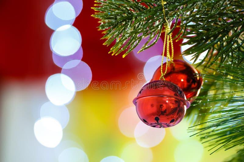 Klirrklockor på julgranen med abstrakt ljus bakgrund arkivbilder
