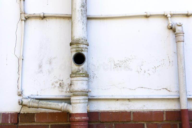 Kloak- och vattenrör på väggen av uppehållet arkivfoto