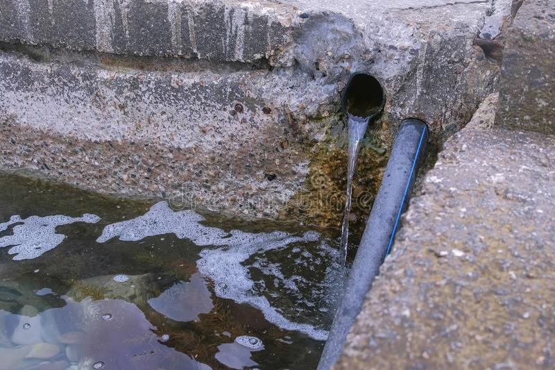 Kloakavloppsvatten, smutsigt och skummande med kemikalieer, urladdning av industriellt in i en stadskanal arkivbilder
