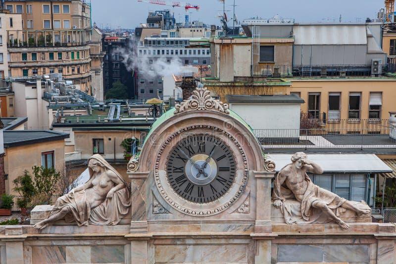 Klock och skulpturer på fasaden av Veneranda Fabbrica del Duomo arkivbild