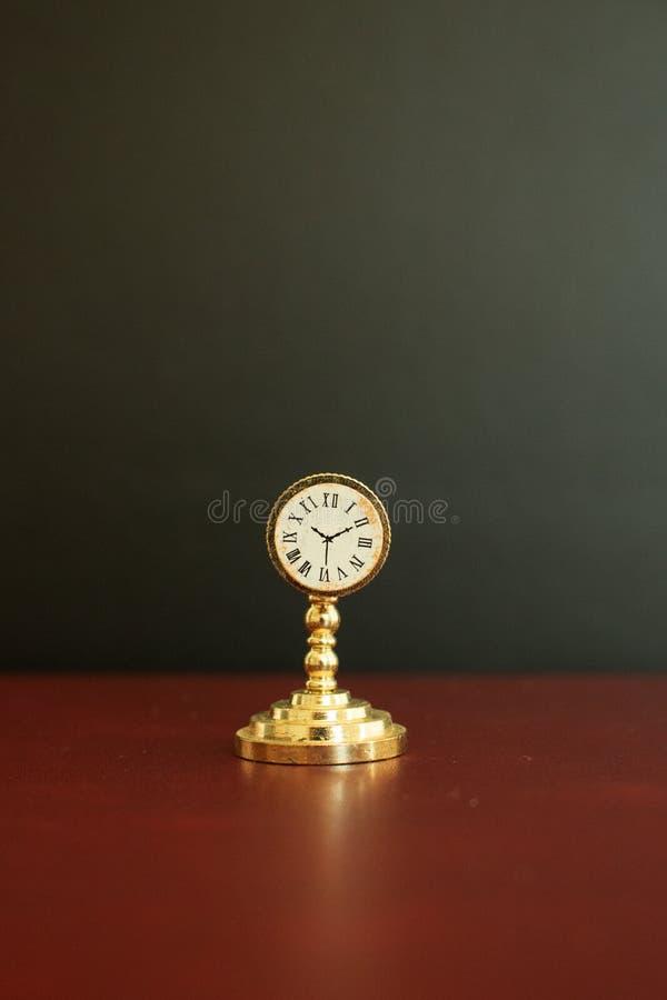 Klocka eller en klocka för gammal guld- tappning en miniatyr royaltyfri fotografi