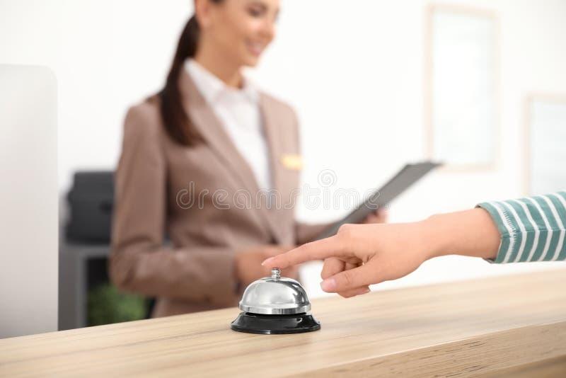 Klocka för tryckande på service för gäst på skrivbordet nära receptionist i hotellet, closeup royaltyfria bilder