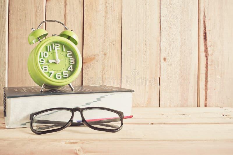 Klocka, glasögon och ordbok på trätabellen arkivfoto