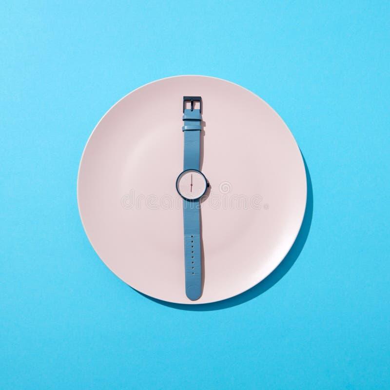 Klocka med tid sex klockan på en vit platta på en blå bakgrund Begreppet av att begränsa intaget av mat bantar och arkivbild