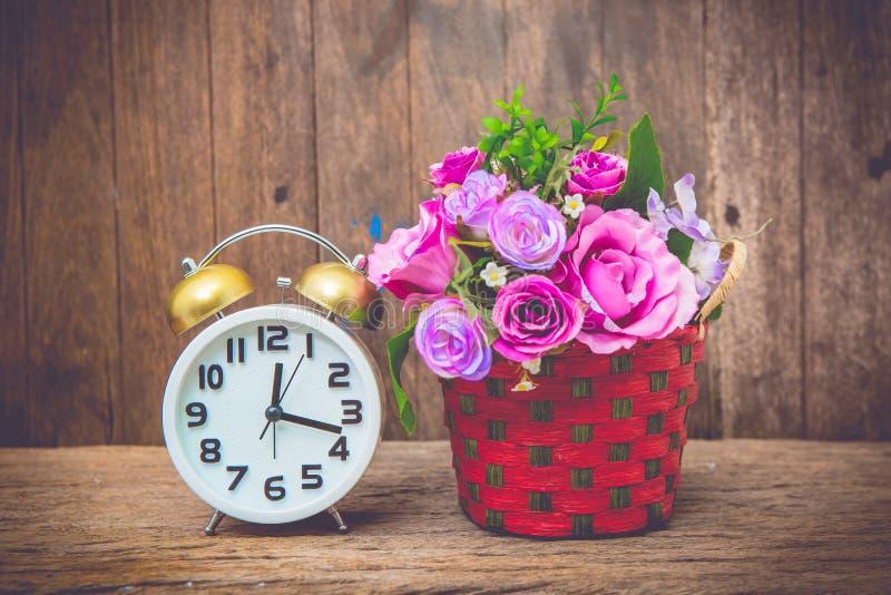 Klocka och blomma arkivbilder