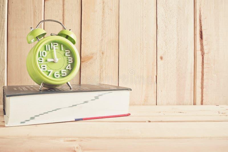 Klocka och ordbok på trätabellen över wood bakgrund royaltyfria foton