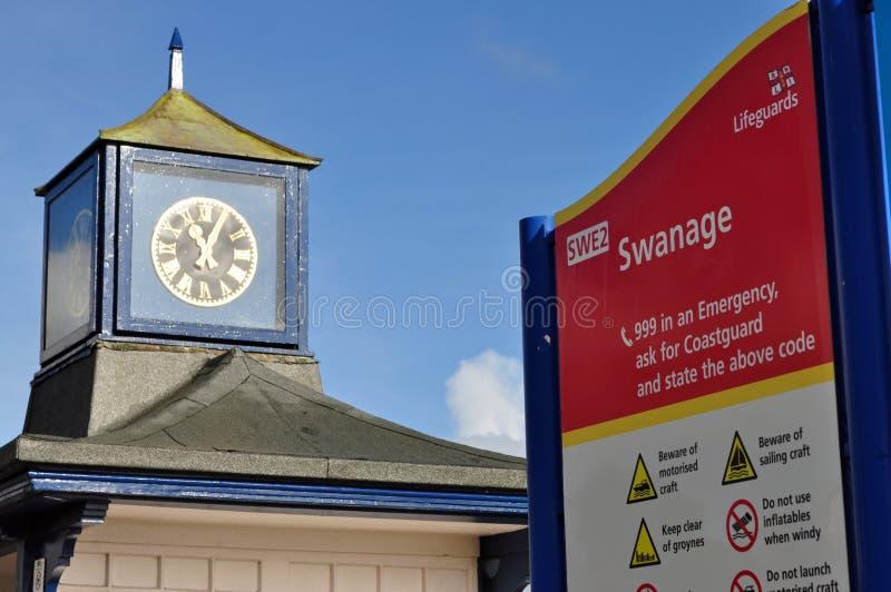 Klocka- och Swanage strandtecken arkivfoton