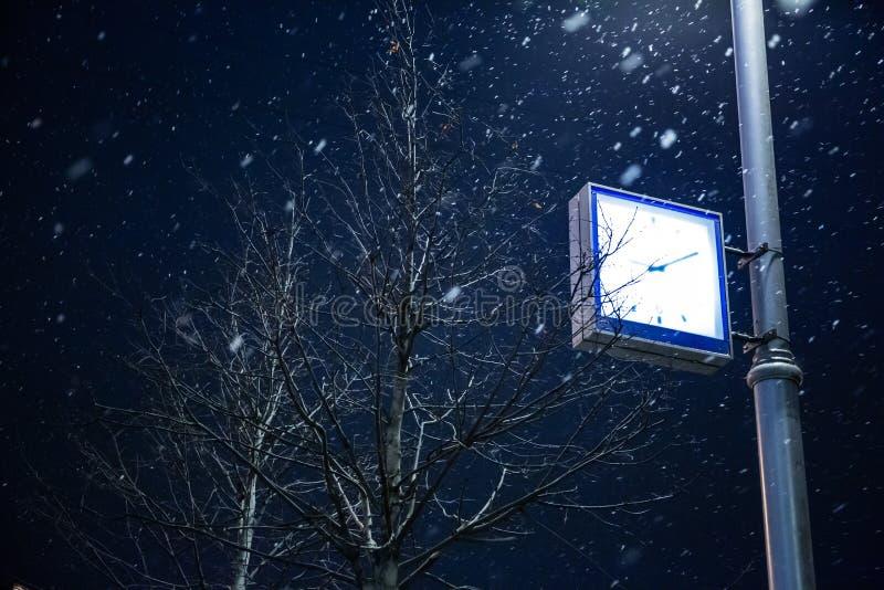 Klocka på en lyktstolpeMoskva i vinter royaltyfri fotografi