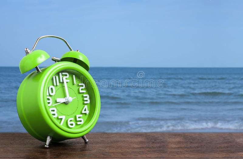 Klocka på trägolv med blå havsbakgrund arkivbild
