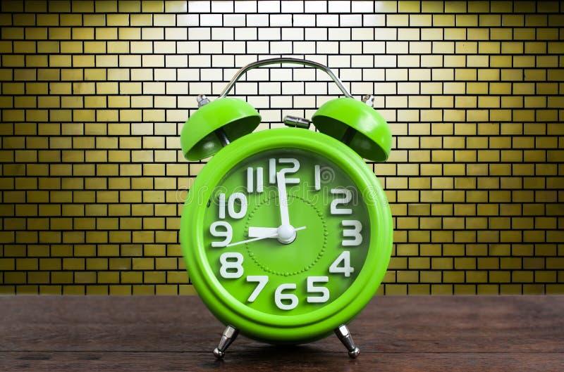 Klocka på trägolv med gul bakgrund för tegelstenvägg royaltyfria bilder