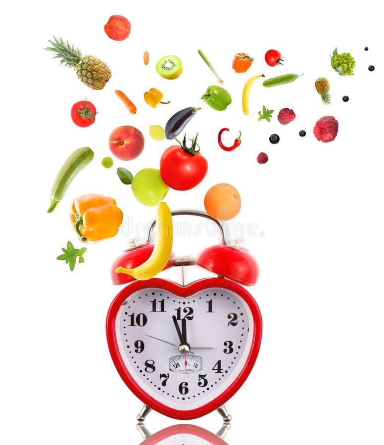 Klocka som hjärta med frukter och grönsaker. arkivbild