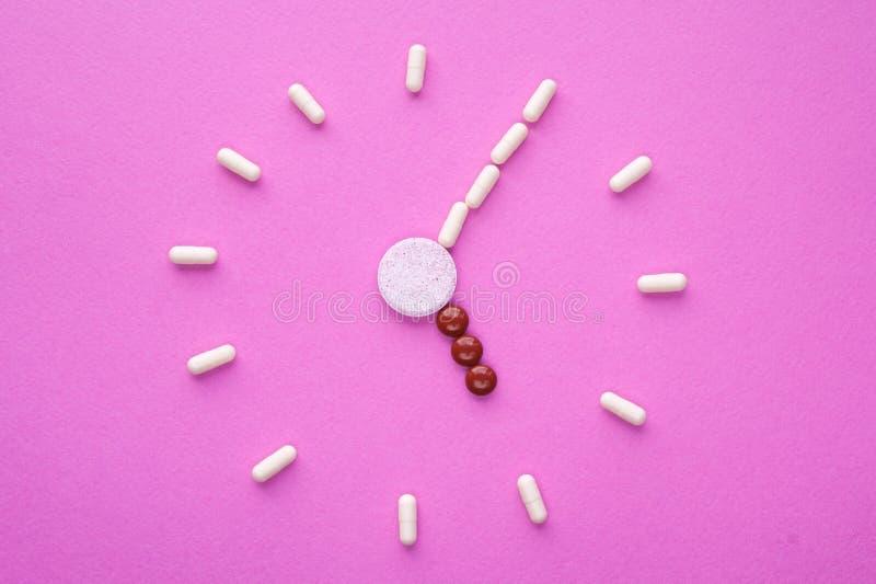 Klocka som skapas från vita piller och bruna minnestavlor på rosa bakgrund Rätt tid för att använda mediciner arkivbild