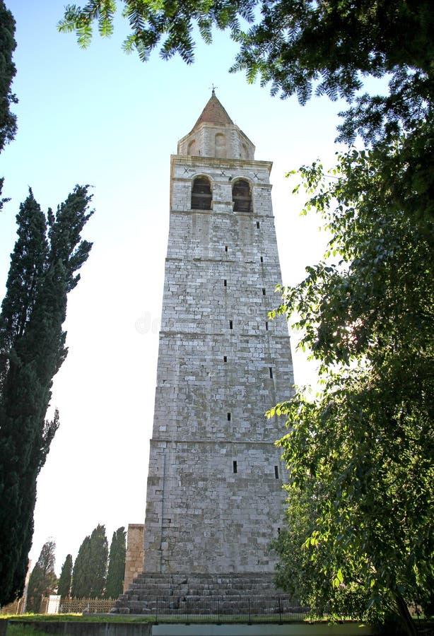 Klocka torn av staden av AQUILEIA i panelljus royaltyfria foton