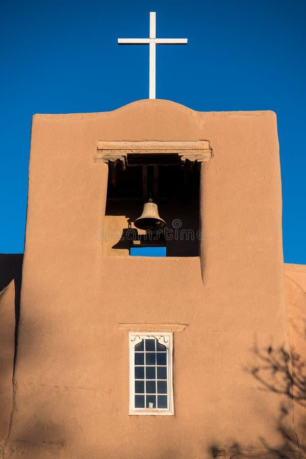 Klocka torn och kors på en spansk beskickningkyrka för historisk Adobe i de amerikanska sydvästerna royaltyfri bild