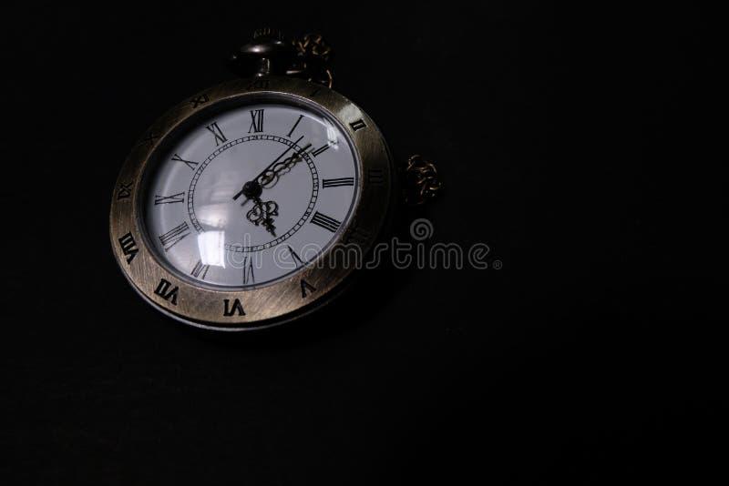 Klockan b?r en antik p?se som f?rl?ggas p? en svart bakgrund royaltyfri fotografi